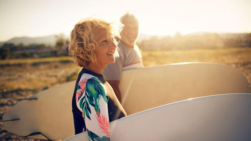 Very active senior couple getting ready to surf the waves on their active vacation.