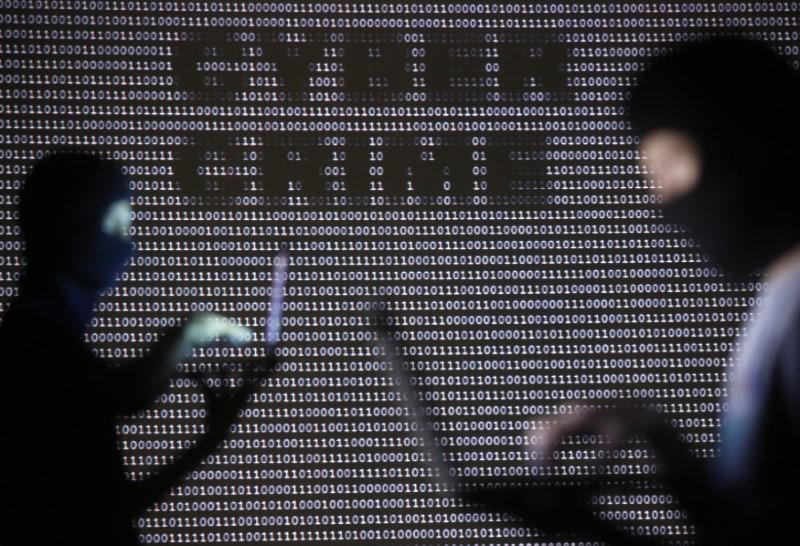Picture illustration of People posing with laptops in front of projection with word 'cyber' and binary code in Zenica