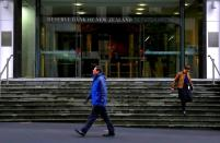 FILE PHOTO: Pedestrians walk near the main entrance to the Reserve Bank of New Zealand located in central Wellington, New Zealand