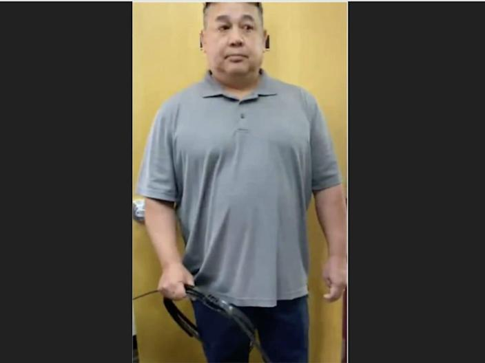 A man with a grayish short-sleeved shirt standing against a yellow backdrop. In his right hand, he is carrying black zip-tie handcuffs.