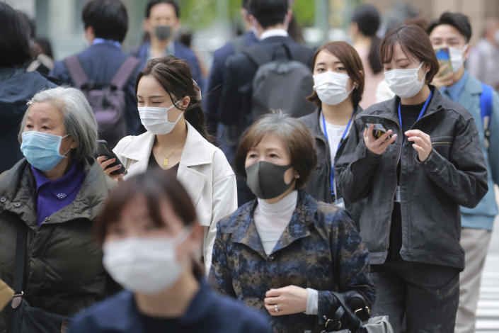 People wearing face masks to protect against the spread of the coronavirus walk on a street in Tokyo, Tuesday, April 13, 2021. (AP Photo/Koji Sasahara)