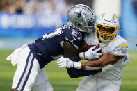 Los Angeles Chargers running back Austin Ekeler, right, is tackled by Dallas Cowboys safety Jayron Kearse during the first half of an NFL football game Sunday, Sept. 19, 2021, in Inglewood, Calif. (AP Photo/Gregory Bull )