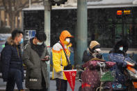 Commuters wearing face masks to protect against the spread of the coronavirus wait at an intersection during a snowy morning in Beijing, Tuesday, Jan. 19, 2021. A Chinese province near Beijing grappling with a spike in coronavirus cases is reinstating tight restrictions on weddings, funerals and other family gatherings, threatening violators with criminal charges. (AP Photo/Mark Schiefelbein)