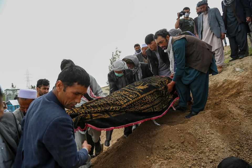Mourners carry a covered dead body during a burial ceremony following a suicide attack in a maternity hospital, at a cemetery in Kabul on May 13, 2020. - The combined death toll from two attacks in Afghanistan, including one on a hospital in which infants and nurses were killed, has risen to 56, health officials said May 13. Three gunmen stormed a Kabul maternity hospital on May 12 as parents brought infants and children for appointments. (Photo by STR / AFP) (Photo by STR/AFP via Getty Images)