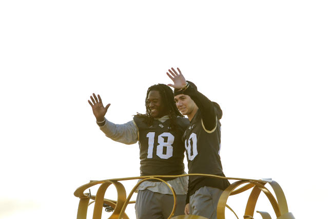 "Central Florida football players <a class=""link rapid-noclick-resp"" href=""/ncaaf/players/228732/"" data-ylk=""slk:Shaquem Griffin"">Shaquem Griffin</a>, left, and McKenzie Milton wave to fans during the a parade at Walt Disney World in the Magic Kingdom on Sunday, Jan. 7, 2018, in Orlando, Fla. (Jacob Langston/Orlando Sentinel via AP)"