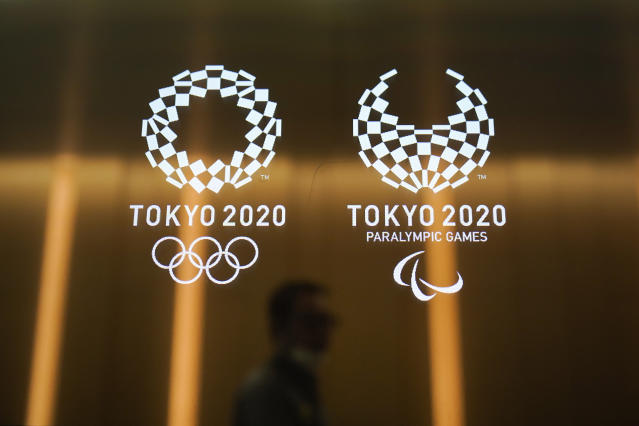 FILE - In this June 11, 2019, file photo, a man walks past the Tokyo 2020 Olympic logos, in Tokyo. Tokyo is building eight new venues. The other 35 venues are defined as temporary or older buildings being reused. (AP Photo/Jae C. Hong, File)
