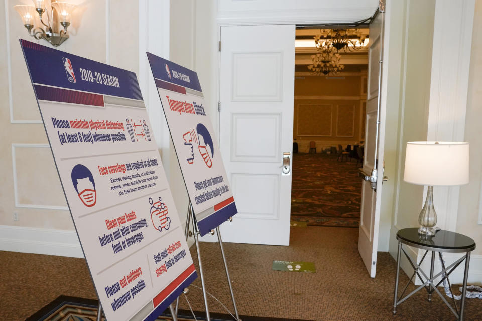 FILE - In this July 29, 2020, file photo, signs lead to an NBA COVID-19 testing site inside ther NBA bubble in Lake Buena Vista, Fla. The NBA wants to be back in December. A new set of rules are coming in just about every sport, almost all with enhanced health and safety in mind. If they work, games could get out of bubbles and return to arenas and stadiums with some fans in attendance sometime soon. (AP Photo/Ashley Landis, FIle)