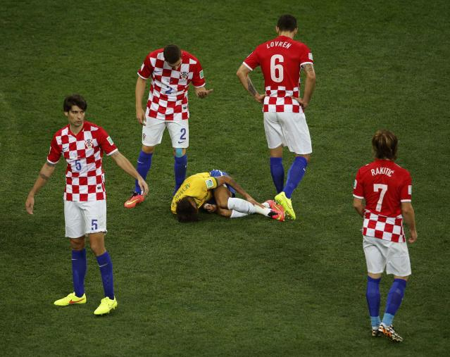 Brazil's Neymar lies on the pitch after being fouled by Croatia's Vedran Corluka (L) during their 2014 World Cup opening match at the Corinthians arena in Sao Paulo June 12, 2014. Corluka was shown a yellow card for the action REUTERS/Paulo Whitaker (BRAZIL - Tags: SOCCER SPORT WORLD CUP TPX IMAGES OF THE DAY)