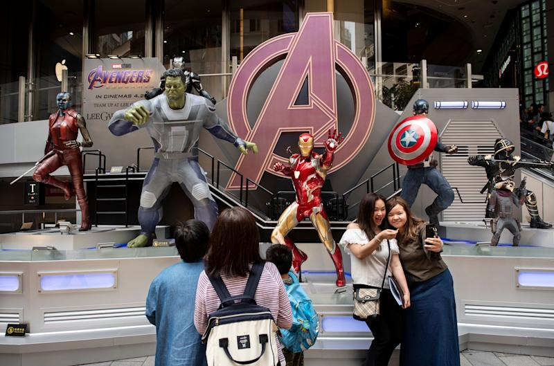 "HONG KONG - 2019/04/26: Pedestrians are seen taking a selfie with Marvel and Marvel Studios figures owned by Disney to commemorate and advertise of the ""Avengers: Endgame"" movie in Hong Kong. (Photo by Budrul Chukrut/SOPA Images/LightRocket via Getty Images)"