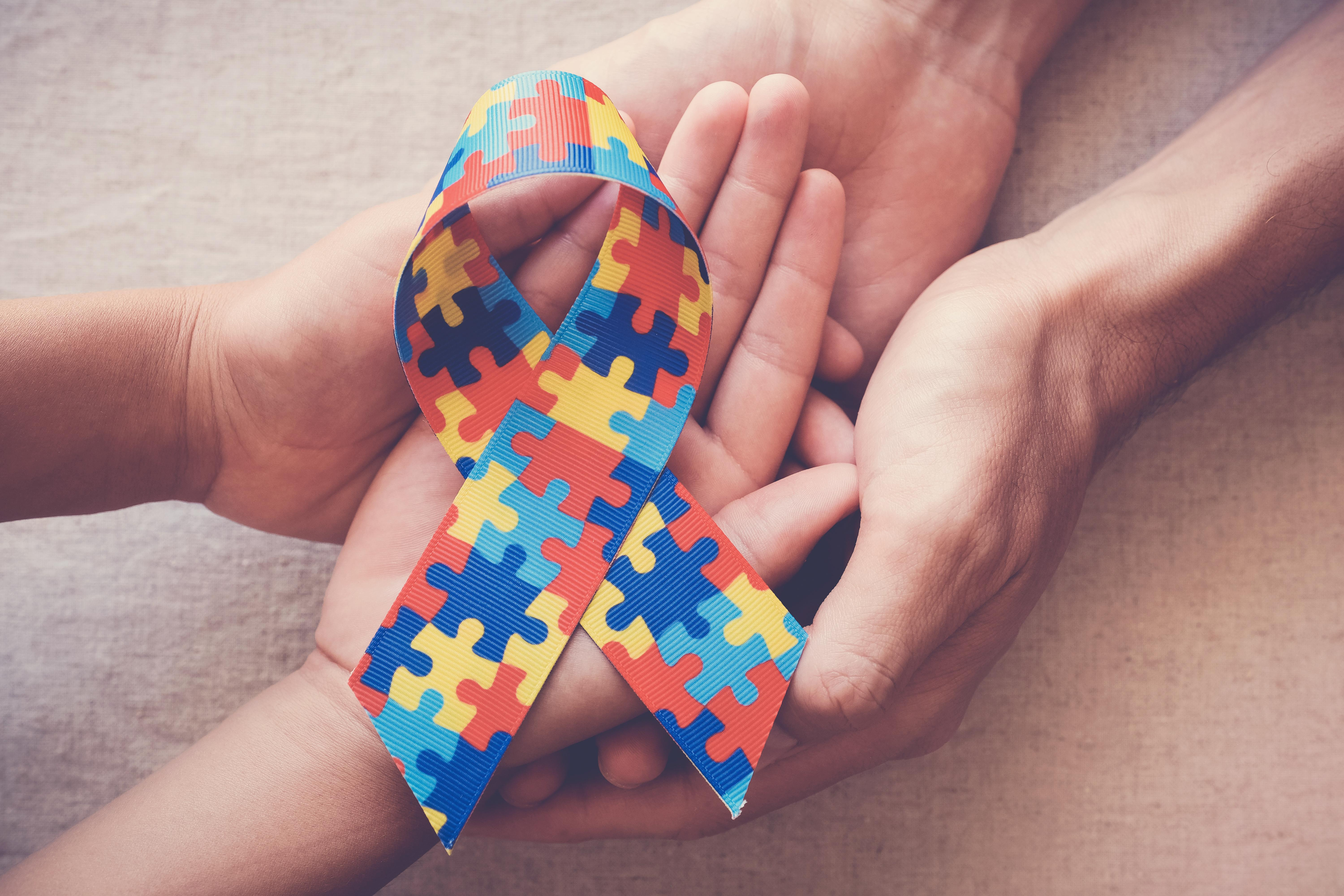 Hands holding puzzle ribbon for autism awareness