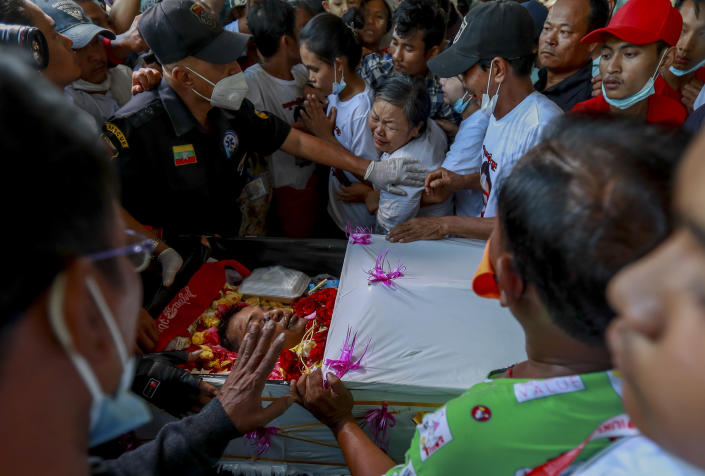 Tin Tin Win, center, weeps over the body of her son, Tin Htut Hein, at his funeral in Yangon, Myanmar, Wednesday, Feb. 24, 2021. Tin Htut Hein was shot on Saturday, Feb. 20, while acting as a volunteer guard for a neighborhood watch group that was set up over fears that authorities were using criminals released from prison to spread fear and commit violence. (AP Photo)