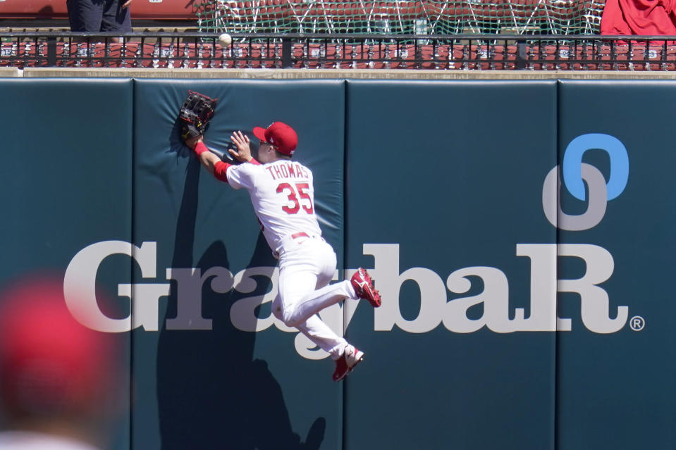 St. Louis Cardinals center fielder Lane Thomas leaps after a two-run home run by Washington Nationals' Ryan Zimmerman during the third inning of a baseball game Wednesday, April 14, 2021, in St. Louis. (AP Photo/Jeff Roberson)