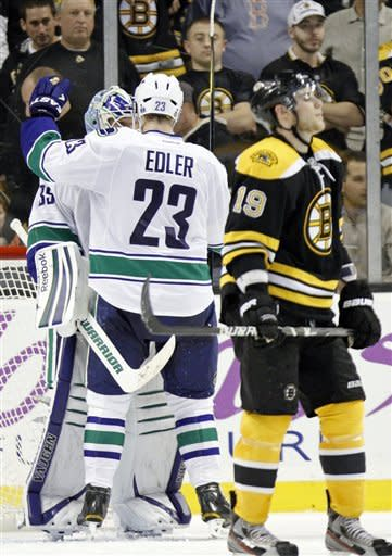 Vancouver Canucks goalie Cory Schneider, left, and Alexander Edler (23) celebrate as Boston Bruins' Tyler Seguin (19) skates past after the Canucks beat the Bruins 4-3 in an NHL hockey game in Boston, Saturday, Jan. 7, 2012. (AP Photo/Michael Dwyer)
