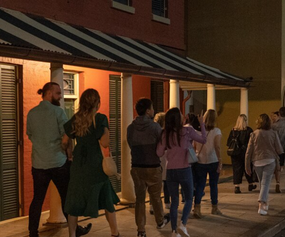A group of people walk infront of a heritage-listed building at night.
