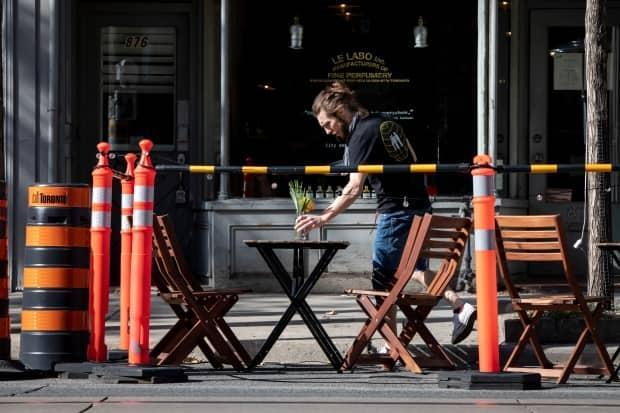 A server prepares a patio dining space for patrons on Queen St. W in Toronto last September. Ontario is easing some restrictions in regions, including allowing outdoor dining in grey-lockdown zones.  (Evan Mitsui/CBC - image credit)