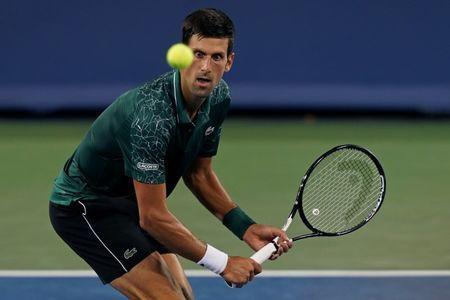 Aug 13, 2018; Mason, OH, USA; Novak Djokovic (SRB) returns a shot against Steve Johnson (USA) in the Western and Southern tennis open at Lindner Family Tennis Center. Aaron Doster-USA TODAY Sports