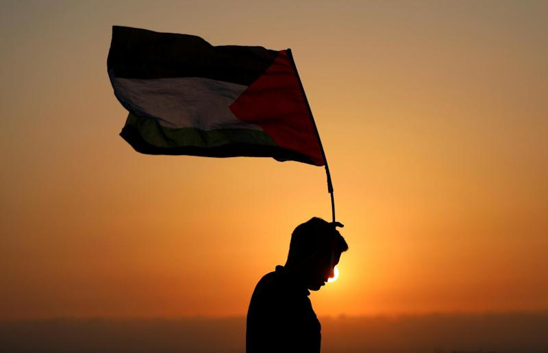 A demonstrator holds a Palestinian flag during a protest against Jewish settlements in the village of Ras Karkar, near Ramallah in the occupied West Bank August 30, 2018. REUTERS/Mohamad Torokman