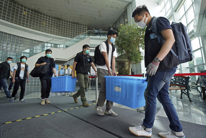Police remove evidence from inside the Apple Daily newspaper headquarters after media tycoon and the newspaper's founder Jimmy Lai, who founded local newspaper Apple Daily, is arrested by police officers at his home in Hong Kong, Monday, Aug. 10, 2020. Hong Kong police arrested Lai and raided the publisher's headquarters Monday in the highest-profile use yet of the new national security law Beijing imposed on the city after protests last year. (Apple Daily via AP)