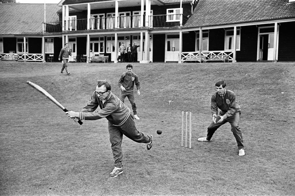 England football team at Roehampton training camp during the 1966 World Cup tournament. A bespectacled Nobby Stiles tries his hand at batting during a game of cricket with Martin Peters as wicket keeper, 21st July 1966. (Photo by Monte Fresco/Mirrorpix/Getty Images)