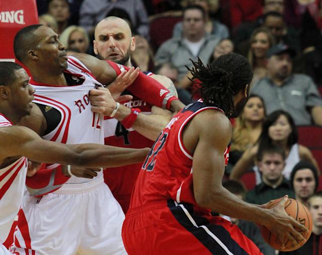 Houston Rockets center Dwight Howard, second from left, is grabbed by Washington Wizards center Marcin Gortat (4) as Wizards' forward Nene, right, goes to the basket guarded by Rockets forward Terrence Jones, left, during the second half of an NBA basketball game in Houston, Wednesday, Feb. 12, 2014. (AP Photo/Richard Carson)