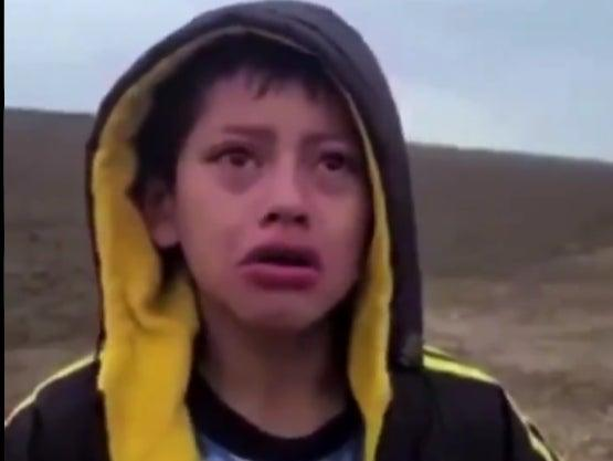 A boy who crossed the border with a group of migrants asks a US Customs and Border Protection guard for help after spending a night in the desert alone. (US Customs and Border Protection)