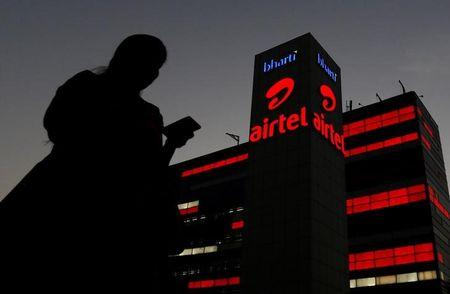A girl checks her mobile phone as she walks past the Bharti Airtel office building in Gurugram on the outskirts of New Delhi, India April 21, 2016. REUTERS/Adnan Abidi/File Photo