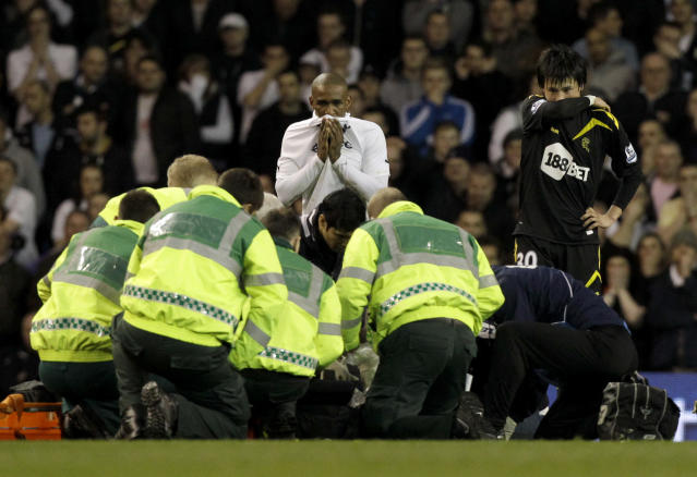 Bolton Wanderers' Fabrice Muamba is obscured by medical staff trying to resuscitate him after collapsing watched by his teammate Ryo Miyaichi, right, and Tottenham Hotspur's Jermain Defoe, center top, during the English FA Cup quarterfinal soccer match between Tottenham Hotspur and Bolton Wanderers at White Hart Lane stadium in London, Saturday, March 17, 2012. Bolton midfielder Fabrice Muamba has been carried off the field at Tottenham after medics appeared to be trying to resuscitate him during an FA Cup quarterfinal that was abandoned. Muamba went to the ground in the 41st minute with no players around him and the game was immediately stopped. (AP Photo/Matt Dunham)