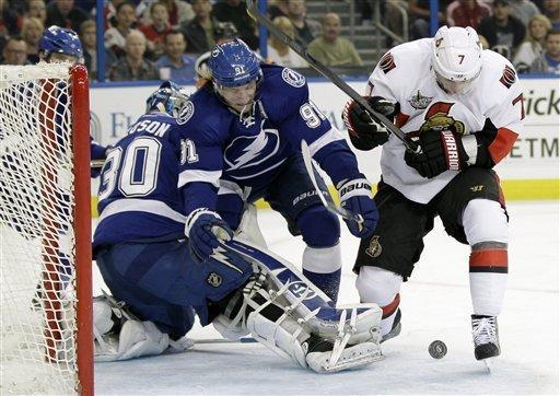 Ottawa Senators center Kyle Turris (7) works against Tampa Bay Lightning center Steven Stamkos (91) for a loose puck in front of Lightning goaltender Dwayne Roloson during the first period of an NHL hockey game Tuesday, March 6, 2012, in Tampa, Fla. (AP Photo/Chris O'Meara)