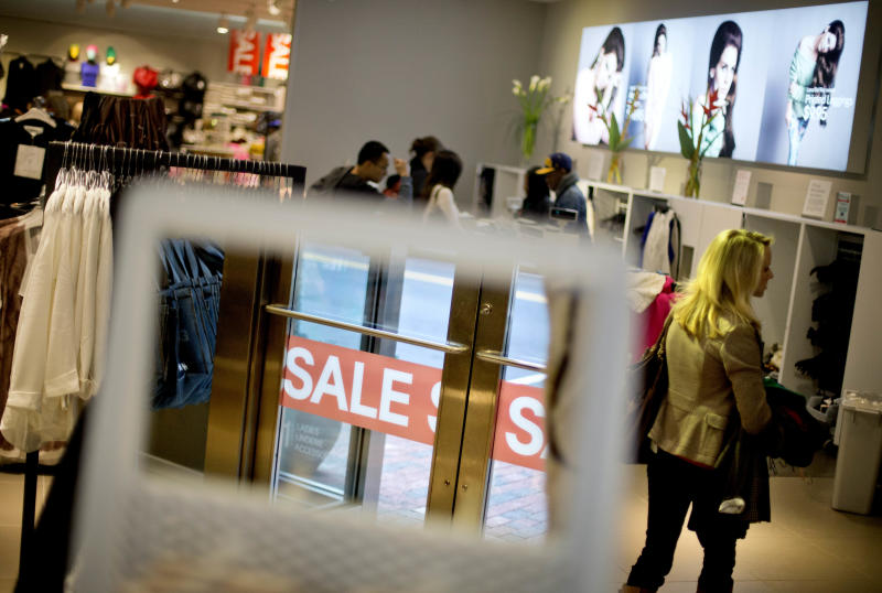 """In this Wednesday, Dec. 12, 2012 photo, a """"Sale"""" sign is reflected in a mirror as a shopper walks though the women's section of an H&M store in Atlanta. The Federal Reserve reports how much consumers borrowed in December on Thursday, Feb. 7, 2013.  (AP Photo/David Goldman)"""
