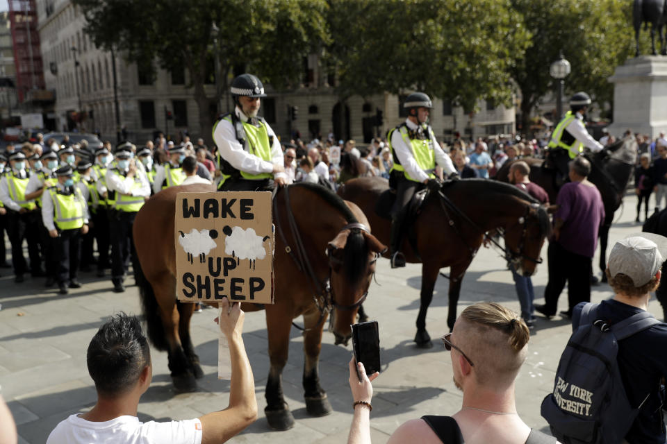 "A protester holds up a placard in front of police officers during a ""Resist and Act for Freedom"" protest against a mandatory coronavirus vaccine, wearing masks, social distancing and a second lockdown, in Trafalgar Square, London, Saturday, Sept. 19, 2020. (AP Photo/Matt Dunham)"