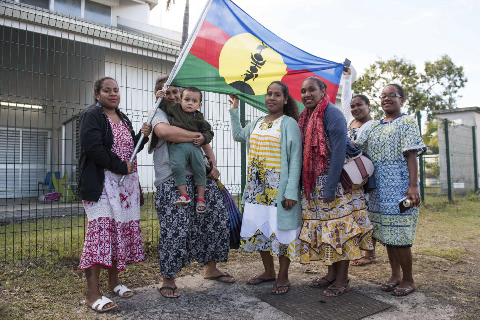 Women supporters for Independence hold the Kanak flag outside a voting station in the Riviere Salee district of Noumea, New Caledonia, Sunday, Oct.4, 2020. Voters in New Caledonia, a French archipelago in the South Pacific, were deciding Sunday whether they want independence from France in a referendum that marks a milestone in a three-decade decolonization effort. If voters choose independence, a transition period will immediately open so that the archipelago can get ready for its future status. Otherwise, New Caledonia will remain a French territory. (AP Photo/Mathurin Derel)