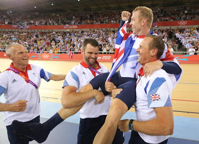 Britain's Chris Hoy is carried by officials as they celebrate after the track cycling men's keirin finals at the Velodrome during the London 2012 Olympic Games August 7, 2012. Hoy won the gold medal. REUTERS/Stefano Rellandini (BRITAIN - Tags: OLYMPICS SPORT CYCLING)