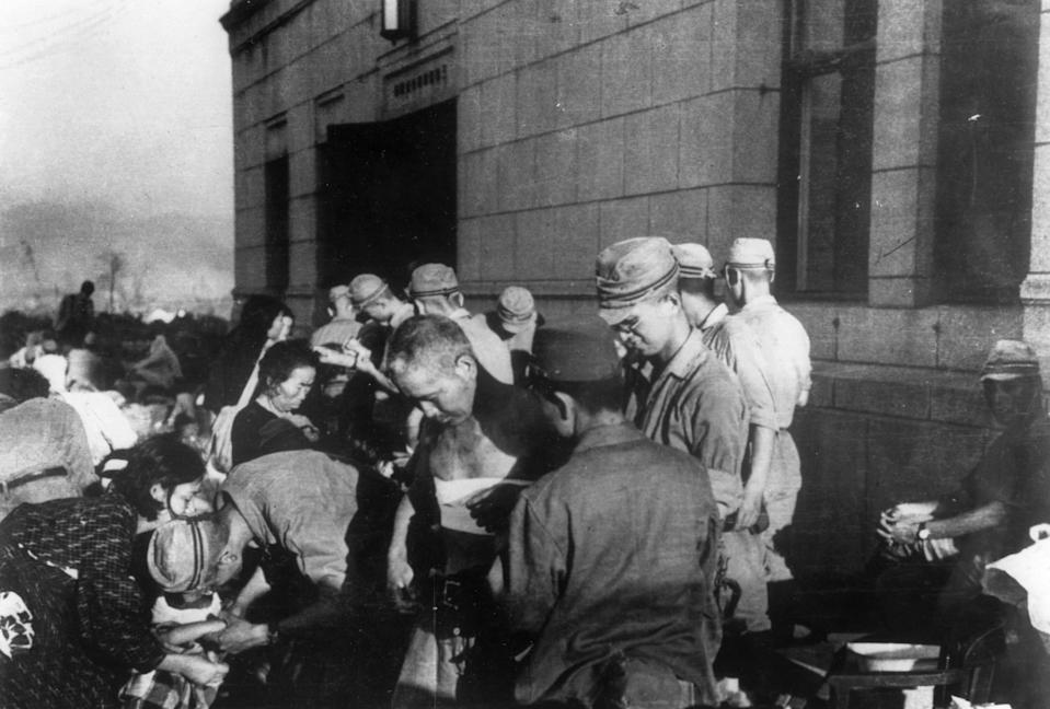 Shortly after the first atomic bomb ever used in warfare was dropped by the United States over the Japanese city of Hiroshima, survivors are seen as they receive emergency treatment by military medics on  Aug. 6, 1945.