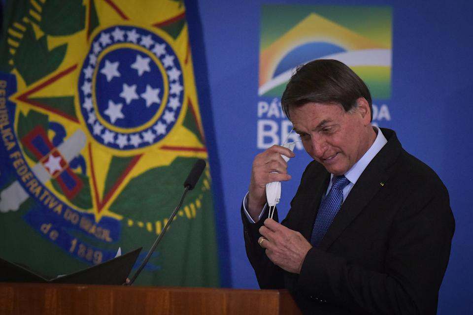 Brazil's President Jair Bolsonaro takes off his face mask to speak during  the Emergency Aid Extension ceremony at the Planalto Palace in Brasília, Brazil, on June 30, 2020. The Emergency Aid is a financial benefit granted by the Federal Government to workers and unemployed people affected by the Coronavirus (COVID-19) pandemic. (Photo by Andre Borges/NurPhoto via Getty Images)