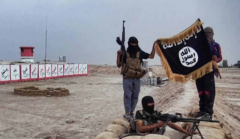 Islamic State militants pose with the trademark jihadist flag after they allegedly seized an Iraqi army checkpoint in the northern province of Salahuddin on June 11, 2014