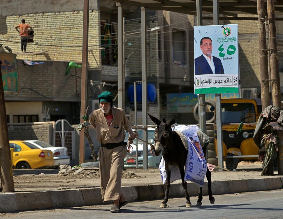 A man and his donkey pass by a campaign poster for the upcoming early parliamentary elections in Baghdad, Iraq, Monday, Sept. 20, 2021. In Iraq, electricity is a potent symbol of endemic corruption, rooted in the country's sectarian power-sharing system. It's perpetuated after each election cycle: Once results are tallied, politicians jockey for appointments in a flurry of negotiations based on the number of seats won. (AP Photo/Hadi Mizban)