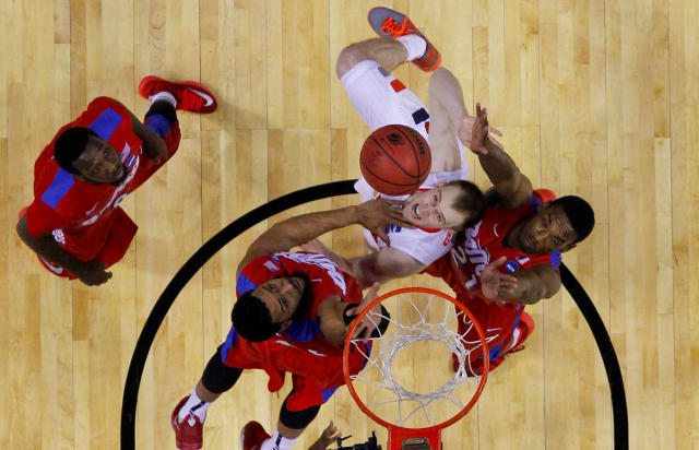 Syracuse's Trevor Cooney (10) shoots between Dayton's Devon Scott, second from left, and Dyshawn Pierre, right, as Khari Price, left, watches during the first half of a third-round game in the NCAA men's college basketball tournament in Buffalo, N.Y., Saturday, March 22, 2014. (AP Photo/Bill Wippert)