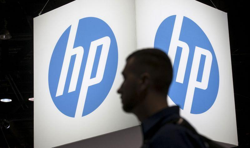 An attendee at the Microsoft Ignite technology conference walks past the Hewlett-Packard (HP) logo in Chicago