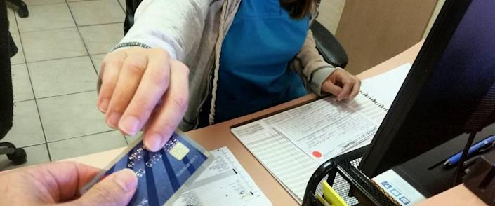 Close up of hand passing over card with a chip to a receptionist at a medical centre in scrubs.