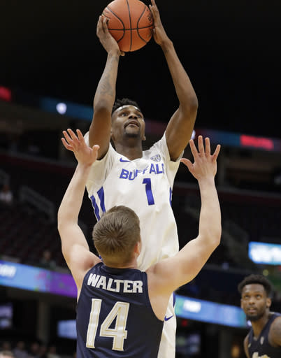 Buffalo's Montell McRae (1) shoots over Akron's Scott Walter (14) during the second half of an NCAA college basketball game of the Mid-American Conference tournament, Thursday, March 14, 2019, in Cleveland. Buffalo won 82-46. (AP Photo/Tony Dejak)
