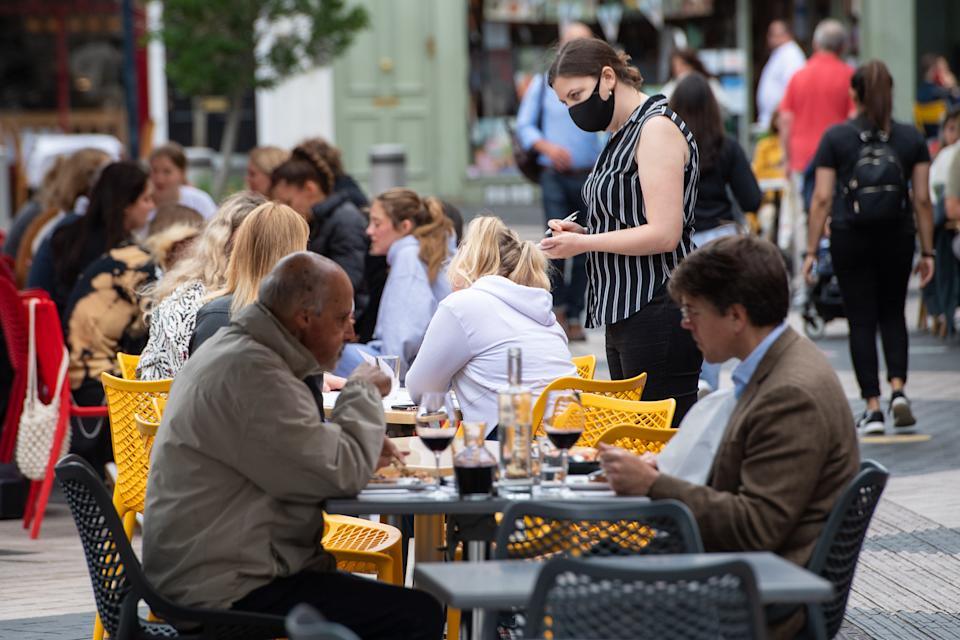 A waitress wearing a face covering serves diners at outside tables in Kensington, London, as the government continues to monitor coronavirus infection levels ahead of potential end to covid restrictions on July 19th. Picture date: Tuesday June 29, 2021. (Photo by Dominic Lipinski/PA Images via Getty Images)