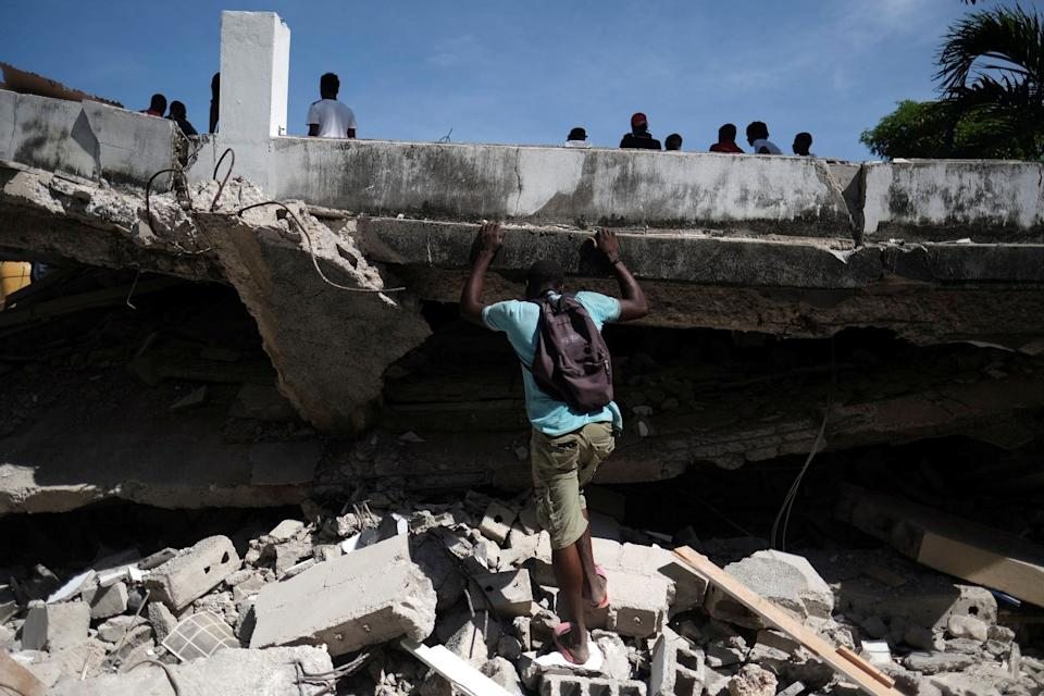 A man searches the site of a collapsed hotel after Saturday's 7.2 magnitude quake, in Les Cayes, Haiti August 16, 2021. REUTERS/Ricardo Arduengo     TPX IMAGES OF THE DAY