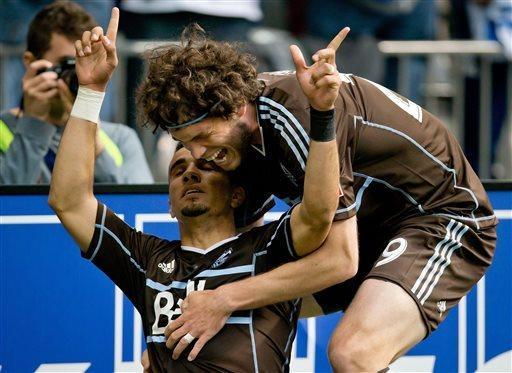 Vancouver Whitecaps' Camilo Sanvezzo, left, of Brazil, and Tom Heinemann celebrate after Sanvezzo scored the tying goal against FC Dallas during the second half of an MLS soccer game in Vancouver, British Columbia, Saturday, April 27, 2013. (AP Photo/The Canadian Press, Darryl Dyck)