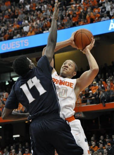 Syracuse's Brandon Triche, right, drives against Monmouth's Tyrone O'Garro during the first half of an NCAA college basketball game in Syracuse, N.Y., Saturday, Dec. 8, 2012. (AP Photo/Kevin Rivoli)