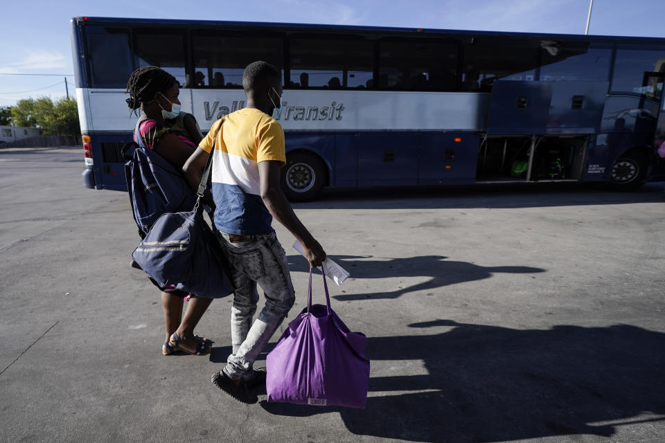 FILE - In this Sept. 22, 2021, file photo Haitian migrants walk toward a bus headed for San Antonio after they were released from United States Border Patrol custody upon crossing the Texas-Mexico border in search of asylum in Del Rio, Texas. Senate aides and immigration advocates say Democrats are considering proposing that the government use its existing parole power to let around 7 million migrants stay in the U.S. temporarily. (AP Photo/Julio Cortez)