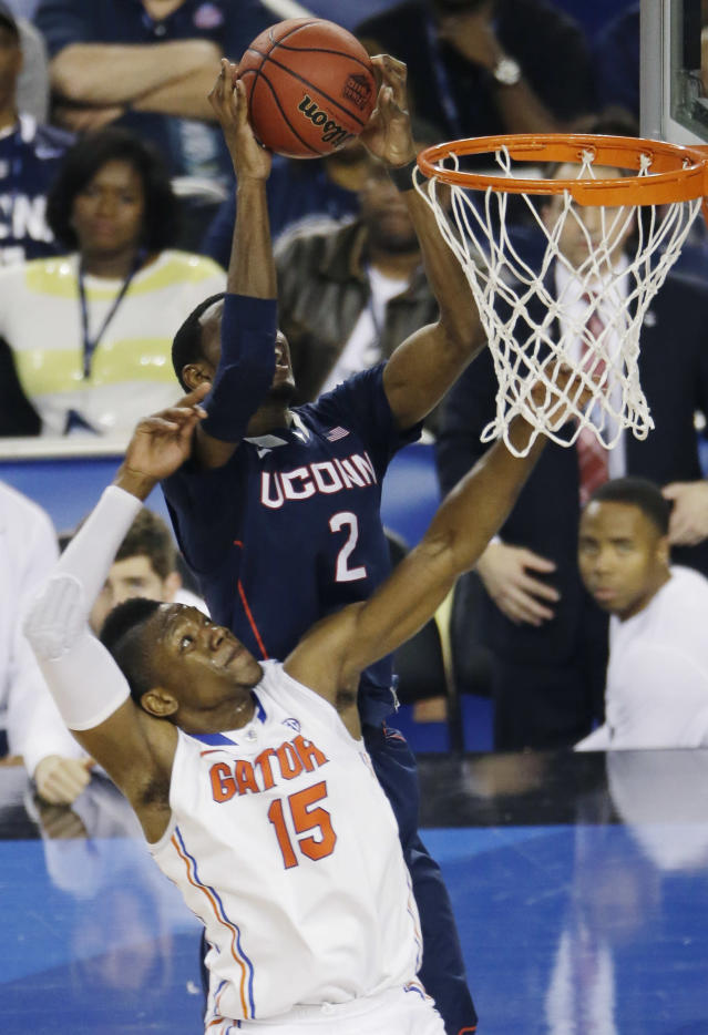 Connecticut forward DeAndre Daniels (2) controls the ball as Florida forward Will Yeguete (15) defends during the second half of the NCAA Final Four tournament college basketball semifinal game Saturday, April 5, 2014, in Arlington, Texas. (AP Photo/Tony Gutierrez)
