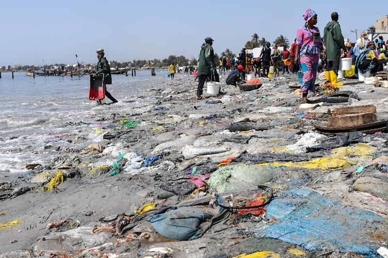 People walk past plastic waste and dead fish on Dakar's Hann Bay in June 2019 (AFP Photo/Seyllou)