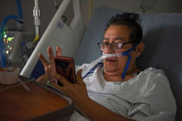 PHOTO: Hector Ortiz-Garcia, 63, who has been hospitalised with COVID-19, texts members of his family from his hospital bed at United Memorial Medical Center (UMMC), during the coronavirus disease (COVID-19) outbreak, in Houston, Texas, July 25, 2020. (Callaghan O'hare/Reuters)