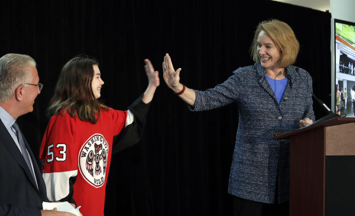 FILE - In this Oct. 8, 2018, file photo, Seattle Mayor Jenny Durkan, right, high-five's Washington Wild hockey team wing Jaina Goscinski, 11, as Tod Leiweke, CEO of NHL Seattle, looks on during a news conference in Seattle. The NHL Board of Governors is meeting, Tuesday, Dec. 4, 2018, in Sea Island, Ga., to give final approval to Seattle's bid to add the league's 32nd team. (AP Photo/Elaine Thompson, File)