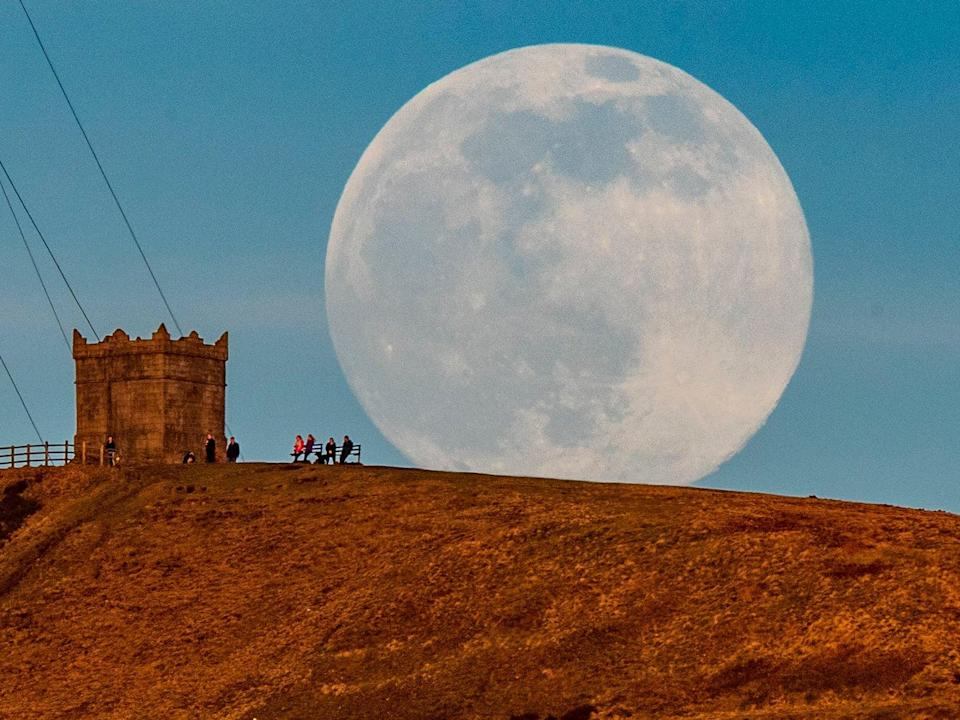 <p>The snow moon rises behind Rivington Pike near Bolton, Greater Manchester.</p> (PA)